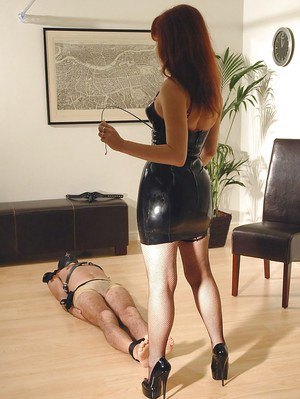 Mature fetish lady in latex dress torturing her male pets dick