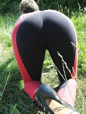 Topless mature femdom in red tights torturing her male pets cock outdoor